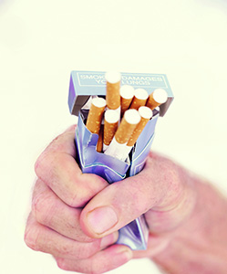 View of man's hand squeezing and crushing a pack of cigarettes