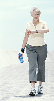 Photo of a senior woman checking the heart rate monitor on her wrist while walking