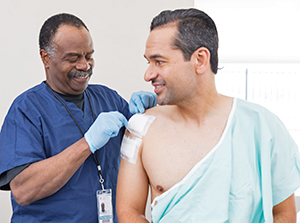 Healthcare provider checking dressings on man's shoulder.